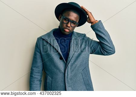 Young african american man wearing elegant style confuse and wonder about question. uncertain with doubt, thinking with hand on head. pensive concept.