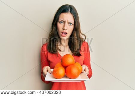 Young brunette woman holding plate with fresh oranges in shock face, looking skeptical and sarcastic, surprised with open mouth