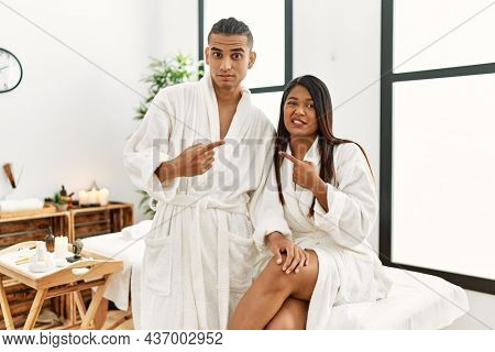 Young latin couple wearing towel standing at beauty center pointing aside worried and nervous with forefinger, concerned and surprised expression