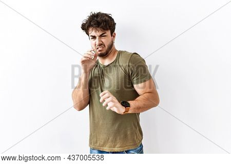 Hispanic man standing over isolated white background disgusted expression, displeased and fearful doing disgust face because aversion reaction.