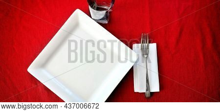 Table setting with fancy plate fork cup and covering cloth for eating red tablecloth