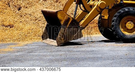Heavy equipment backhoe or bulldozer with pile of dirt wood chips