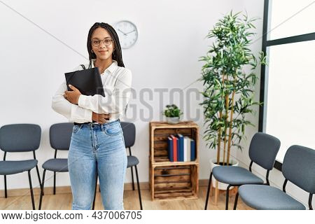 Young african american woman smiling confident holding binder at waiting room
