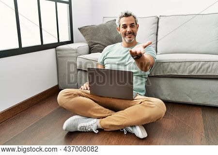 Middle age hispanic man using laptop sitting on the floor at the living room smiling cheerful offering palm hand giving assistance and acceptance.