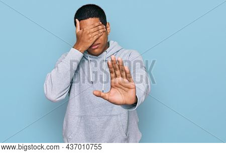 Young handsome hispanic man wearing casual sweatshirt covering eyes with hands and doing stop gesture with sad and fear expression. embarrassed and negative concept.