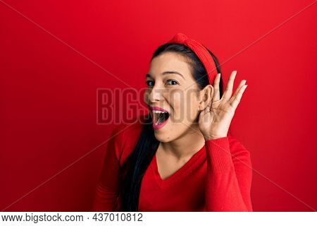 Young latin woman wearing casual clothes smiling with hand over ear listening and hearing to rumor or gossip. deafness concept.