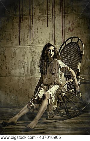 A terrible woman, possessed by the devil, sits on a rocking chair against a concrete wall dripping with blood. Creepy zombie woman. Horror, thriller. Halloween.