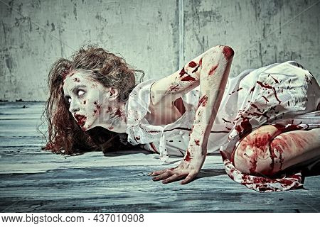 A creepy, devil-possessed woman with pale eyes and tousled hair covering her face and a bloody nightie crawls against a concrete wall. Zombie woman. Horror, thriller. Halloween.