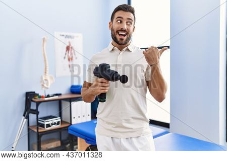 Handsome hispanic man holding therapy massage gun at physiotherapy center pointing thumb up to the side smiling happy with open mouth
