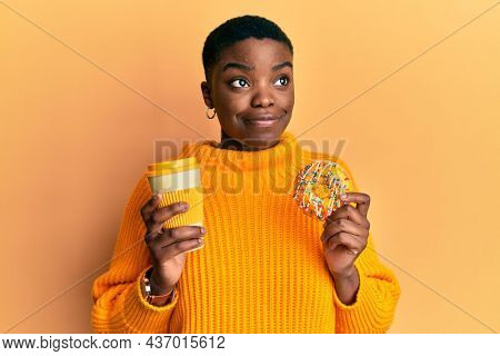 Young african american woman eating doughnut and drinking take away coffee smiling looking to the side and staring away thinking.