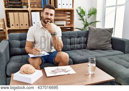 Handsome hispanic man working with rorschach test at psychology clinic looking confident at the camera smiling with crossed arms and hand raised on chin. thinking positive.