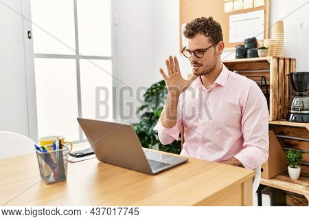 Young hispanic man having video call communicating with deaf sign language at office