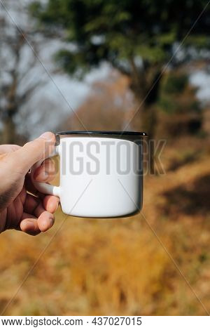 Enamelled Mug Mock Up, Outdoors. Close-up Of Male Hand Showing Empty, Hiking Metal Cup In Forest. Co