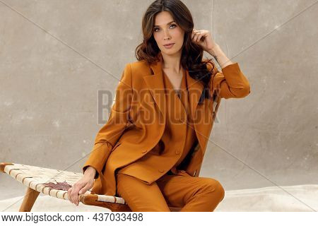 Studio Portrait Of Self Confident Young Female Fashion Model With Long Wavy Hair In Trendy Business