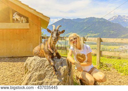 Tourist Girl Playing With A Goat In Maienfeld Village. Deutch Switzerland Of Graubunden Canton Or Gr
