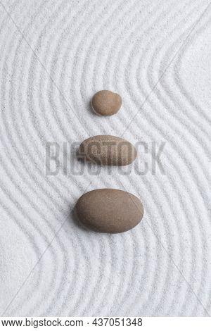 Zen stones white sand background in art of balance concept