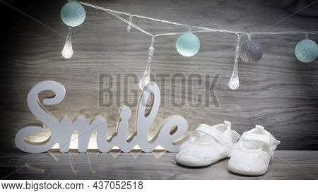 Blue Cotton Bals, Little Child's Shoes And The Word Smile 3d On A Wooden Background