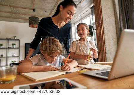 Happy Young Mother And Excited Teen Kids Have Fun Prepare School Assignment Together. Smiling Caucas