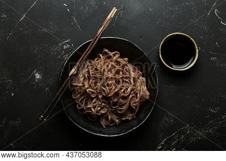 Bowl With Plain Soba Noodles On Dark Black Stone Background From Above, Noodles For Cooking Chinese