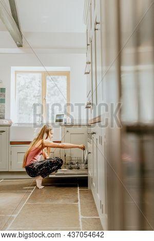 Blond girl unloading dishwasher, basic house chores