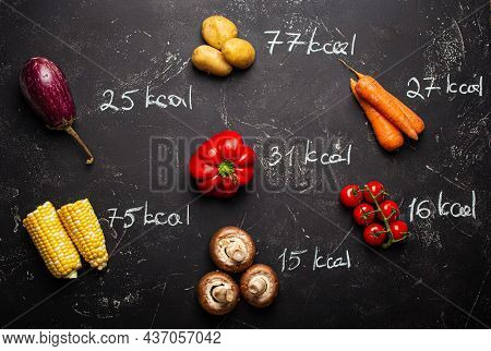 Top View Of Different Vegetables On Black Stone Background And Chalk Wrote Calories Quantity For Wei