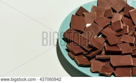 Chopped Dark Chocolate Bars Stack On A Plate Isolated Over White Background. Sweet Junk Food, Desser
