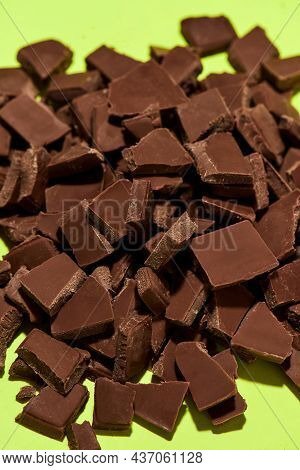 Closeup Of Broken, Crushed Dark Chocolate Bars Stack Isolated Over Green Background. Sweet Junk Food