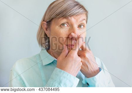 Loss Of Smell. Senior Woman Touches Her Nose With Her Fingers Because Of The Loss Of Her Sense Of Sm