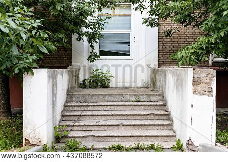 Shabby Stone Porch And Closed Door Of City House On Summer Evening