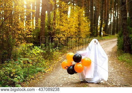 A Child In Sheets With Slits Like A Ghost Costume In An Autumn Forest With Orange And Black Balls Sc