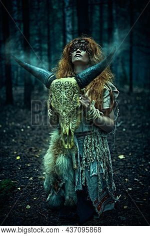Female shaman in an ethnic dress doing a mysterious ritual with an animal skull. Portrait in a dark gloomy forest. Black magic concept, fantasy. Paganism. Halloween.