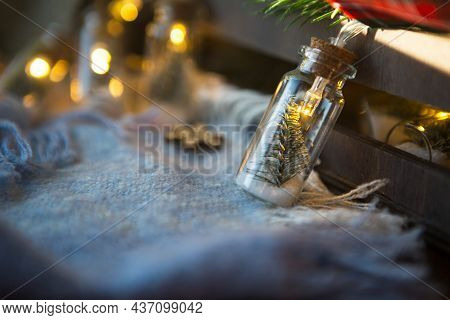 Fairy Lights In A Jar With A Christmas Tree And Snow Close-up On A Warm Cozy Plaid With Wooden Decor