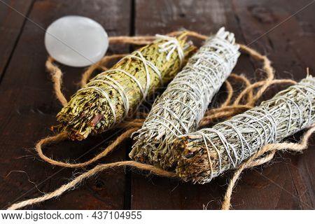 A Close Up Image Of Three Spiritually Healing Smudge Stick With Selenite Palm Stone.