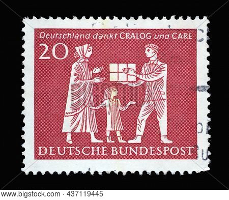 ZAGREB, CROATIA - JUNE 27, 2014: Stamp printed in Germany shows Mother and Child Receiving Gift Parcel, in gratitude for American help during 1946-1962, circa 1963