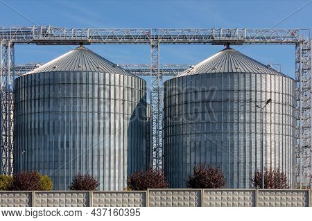 The Huge Metal Tanks Of The Grain Elevator Are Illuminated By Daylight, Surrounded By A Concrete Fen
