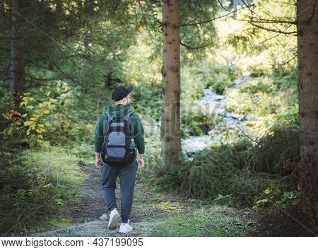 A Man With Backpack Walks In The  Autumn Forest. Hiking Alone Along Autumn Forest Paths. Travel Conc