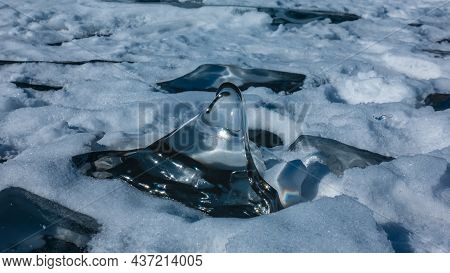 A Transparent Fragment Of Ice, Similar To A Frozen Drop, Lies On The Snow. Highlights On The Edges,