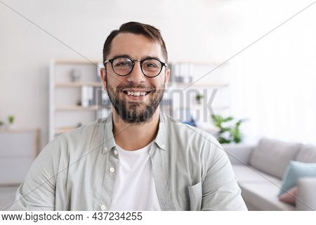 Headshot Of Cheerful Mature European Man With Beard In Glasses Look At Laptop Webcam At Minimalist L