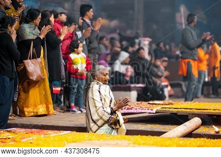 17.12.2019, Varanasi, India. The Sacred Religious Ceremony Of Arati. An Old Woman Stands Praying And