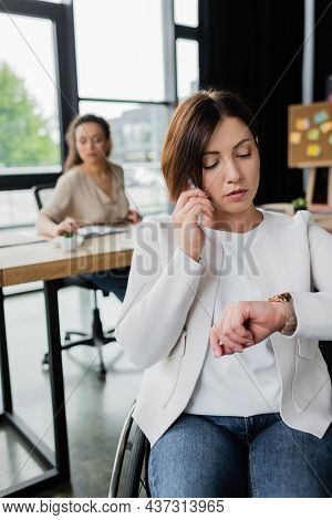 Businesswoman With Disability Looking At Wristwatch During Phone Conversation Near Blurred African A