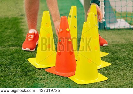 Football Training Cones. Coach Preparing Practice Soccer Field With Red And Yellow Training Cones. S