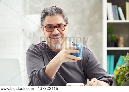 Portrait of happy man at home sitting at desk, working, looking at camera. Happy smile, grey hair, beard, glasses. Portrait of mature age, middle age, mid adult man in 50s.