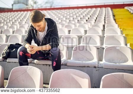 Sporty female sitting alone on the bleachers at the daylight
