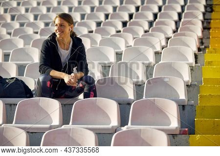 Sporty happy woman sitting alone on the bleachers at the daylight