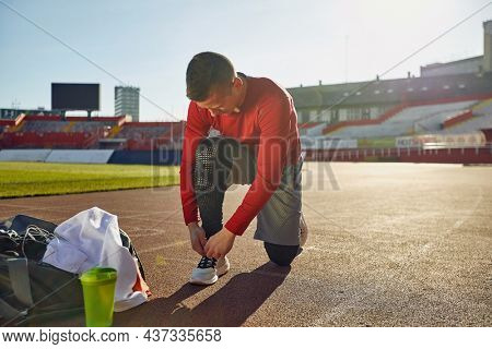 young adult caucasian male kneeling on one knee at the stadium athletic track, tying shoelaces, preparing for training