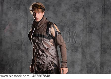 Steampunk Or Post-apocalyptic Style Character, A Young Man In A Grunge Suit. A Jacket With Fastened