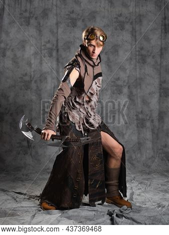 Steampunk Or Post-apocalyptic Style Character, With An Unusual Cold Weapon For Two Hands, A Curved B