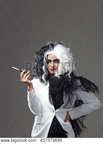 A Charismatic Unusual Woman In A Black And White Outfit With Black And White Hair Smokes A Cigarette