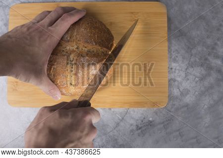 Hands Cutting Loaf Of Bread On Wooden Cutting Board Flat Lay