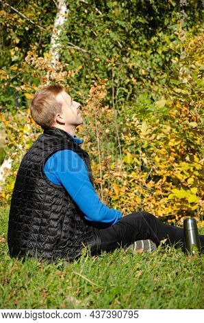 Caucasian Man Sits Next To Thermos In Autumn Park On Background Of Yellow Trees. Autumn Mood Concept